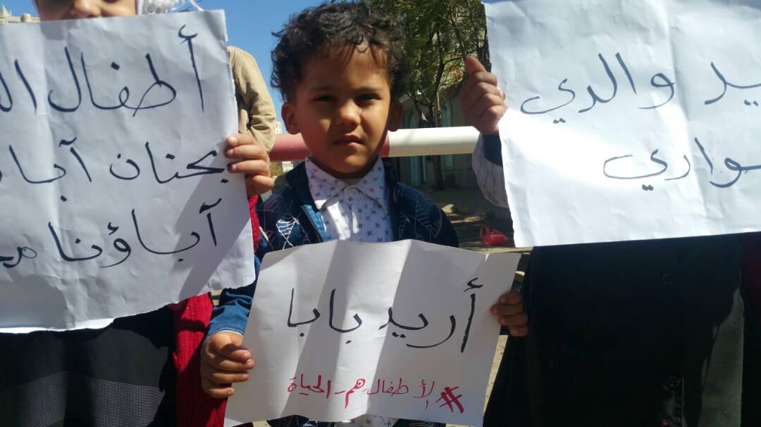 أحد أبناء المختطفين في اليوم العالمي يرفع لوحة كتب عليها اريد بابا