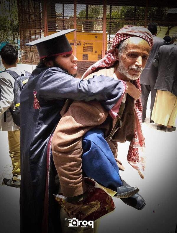تفاعل واسع مع صورة أب يحمل نجله المعاق في حفل تخرج بصنعاء